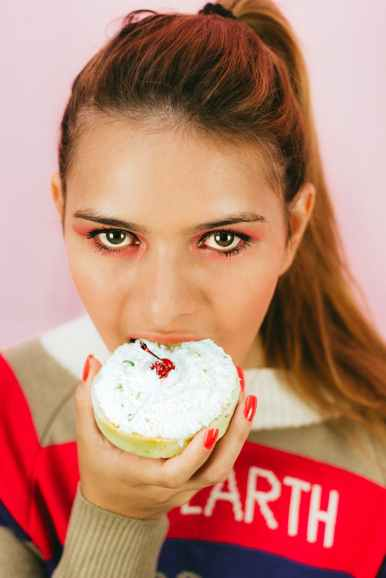 close up photo of woman eating pastry